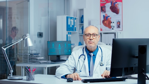 Médico fazendo uma consulta online em uma clínica privada moderna, onde os pacientes estão conversando com enfermeiras. coisas médicas andando em segundo plano. usando a tecnologia da internet e oferecendo aconselhamento médico
