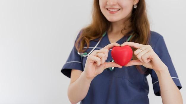 Médico feliz close-up, segurando o brinquedo em forma de coração
