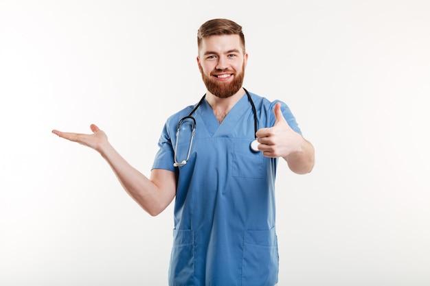 Médico feliz homem amigável apresentando copyspace na palma da mão