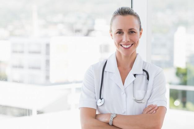 Médico feliz sorrindo para a câmera com os braços cruzados no consultório médico