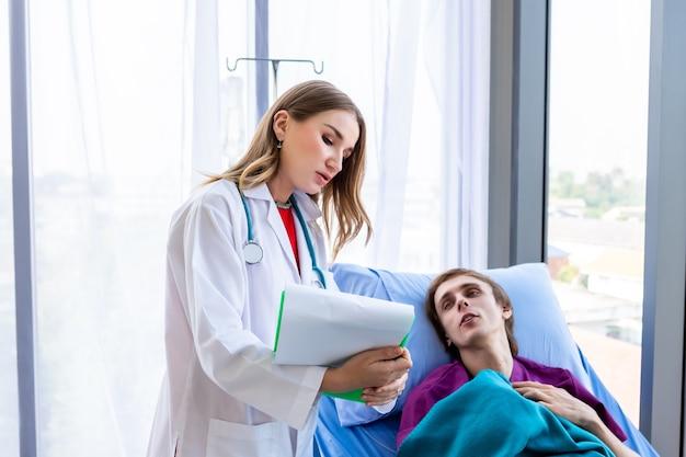 Médico feminino aconselhamento terapêutico com emoções positivas segura a prancheta para um paciente homem na cama em fundo branco de hospital.