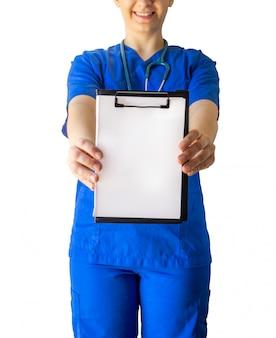 Médico feminino alegre em um uniforme médico azul segurando um papel branco em branco, com um espaço de cópia