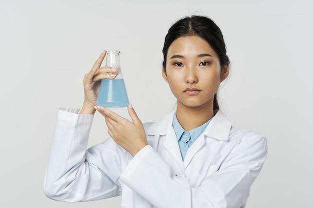 Médico feminino asiático com tubo de ensaio