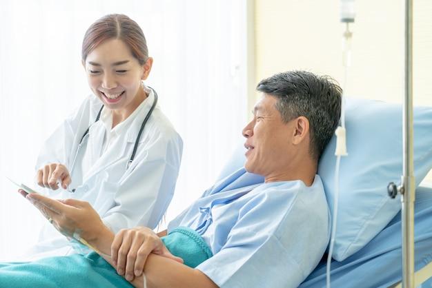 Médico feminino asiático, sentar-se cama hospital, e, discutir, com, paciente sênior