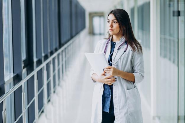 Médico feminino atraente em pé com documentos no hospital