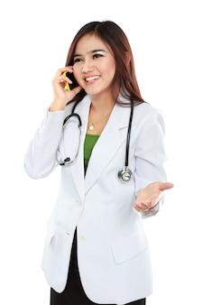 Médico feminino atraente, vestindo jaleco com estetoscópio, falando com o celular