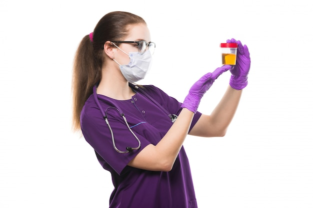 Médico feminino caucasiano atraente, segurando a amostra de urina nas mãos em máscara médica e luvas estéreis