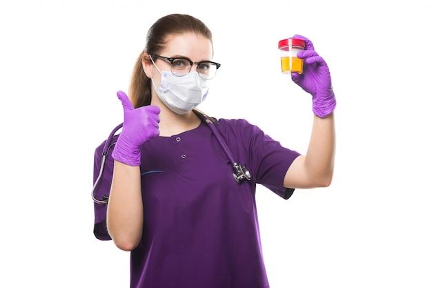 Médico feminino caucasiano atraente, segurando a amostra de urina nas mãos na máscara médica e luvas estéreis com o polegar