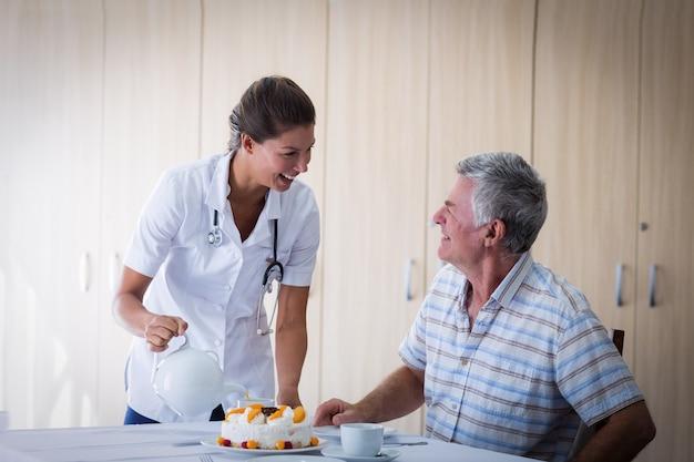 Médico feminino celebração idosos homem aniversário na sala de estar