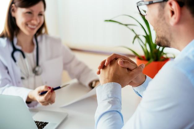 Médico feminino confiante, discutindo o diagnóstico com o paciente no escritório