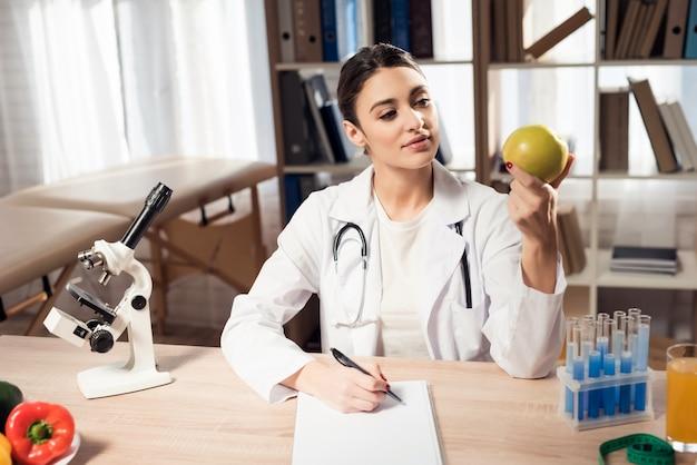 Médico feminino está segurando a apple e escrevendo notas