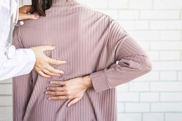Médico feminino, examinando, um, paciente, sofrimento, de, abaixar, dor traseira