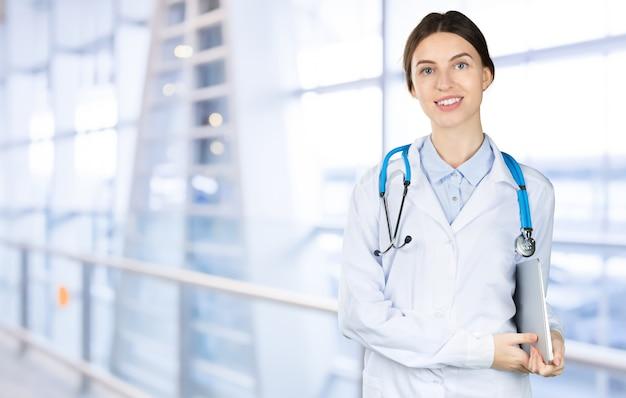 Médico feminino jovem atraente com interior turva hospital no fundo