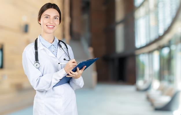 Médico feminino jovem atraente com interior turva hospital