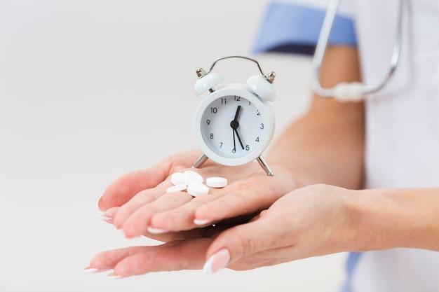 Médico feminino mão segurando comprimidos e um relógio