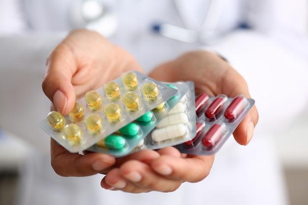 Médico feminino mão segurando o pacote de diferentes