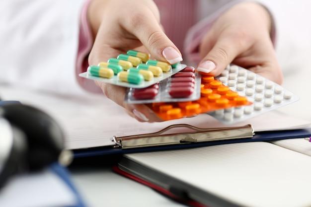 Médico feminino mão segurando pacotes de pílulas diferentes