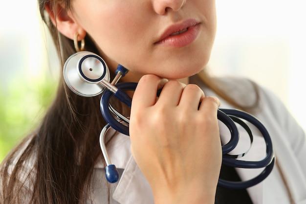 Médico feminino mão segure estetoscópio em roupas médicas