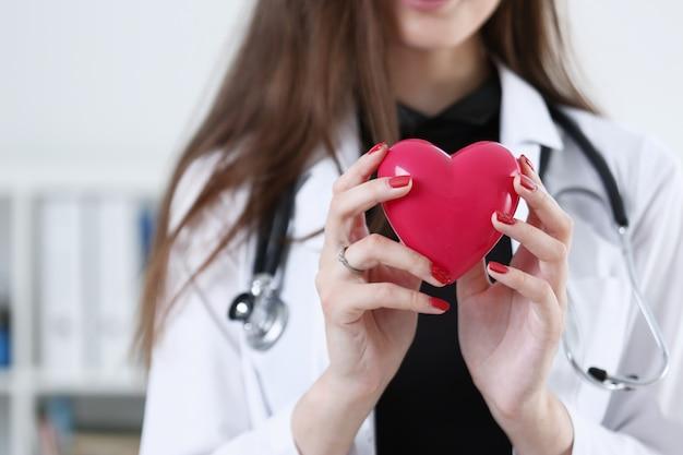 Médico feminino mãos segurando um coração