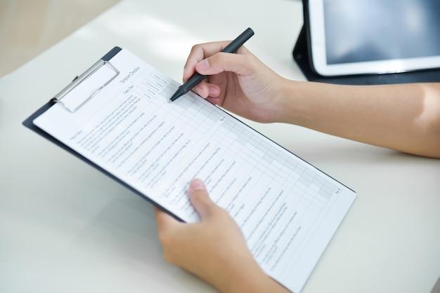 Médico feminino mãos tomando nota na lista de verificação.