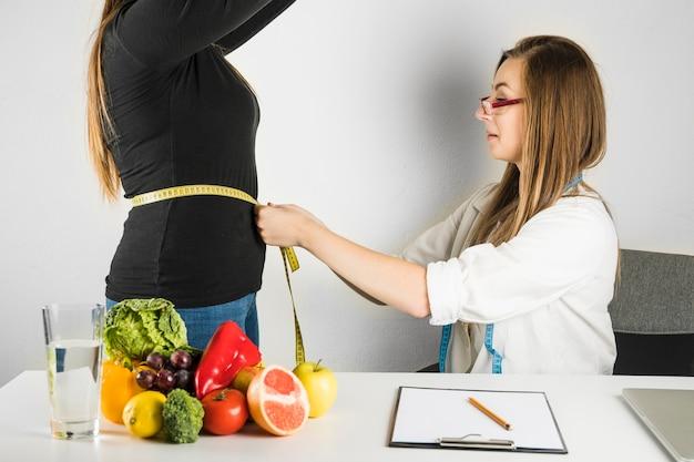 Médico feminino, medindo, cintura, de, mulher, em, clínica