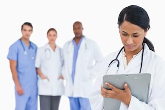 Médico feminino, notas levando, ligado, área de transferência, com, pessoal, membros, atrás de, dela