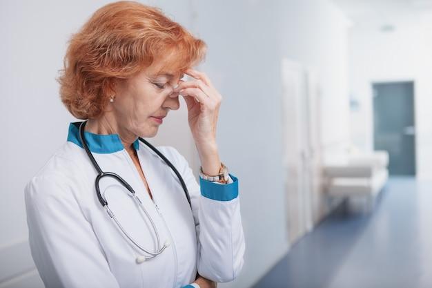 Médico feminino sênior, olhar cansado após um longo dia de trabalho no hospital.