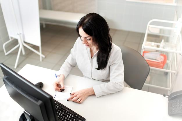 Médico feminino trabalhando no computador portátil, escrevendo o bloco de notas com informações de registro na mesa no hospital ou clínica, cuidados de saúde e conceito médico