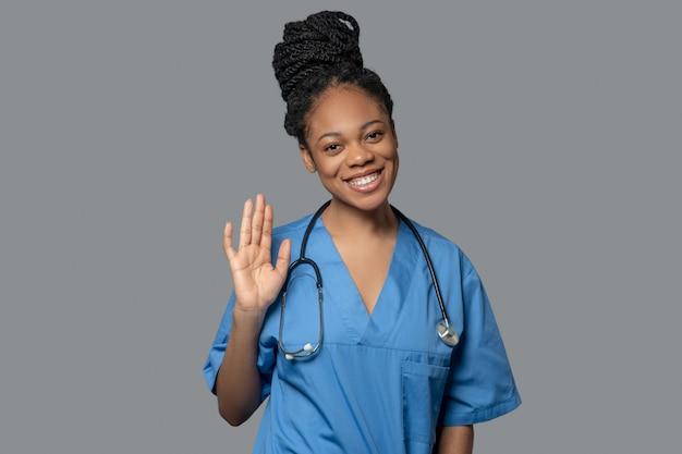 Médico. foto de um jovem médico de pele escura acenando com a mão