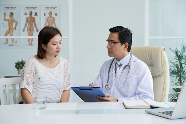 Médico generalista ouvindo reclamações de uma jovem e fazendo anotações em um documento na prancheta