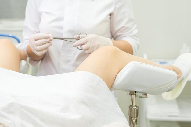 Médico ginecologia examinando paciente do sexo feminino na cadeira ginecológica segurando pinça