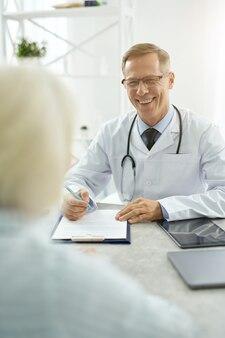 Médico homem alegre conversando com mulher sênior em seu escritório