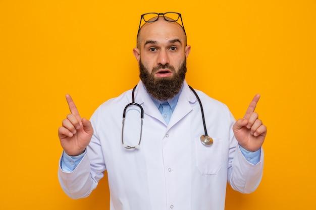 Médico homem barbudo com jaleco branco com estetoscópio no pescoço e óculos na cabeça olhando para a câmera surpreso apontando com o dedo indicador em pé sobre um fundo laranja