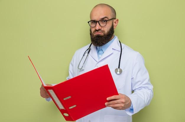 Médico homem barbudo vestindo jaleco branco com estetoscópio no pescoço usando óculos segurando uma pasta do escritório e olhando com uma cara séria