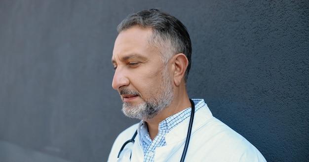 Médico homem caucasiano de cabelos grisalhos cansado tirando a máscara médica e descansando encostado na parede com os olhos fechados. médico masculino descansa depois de muito trabalho. vida perdida. dia difícil do médico. ao ar livre.