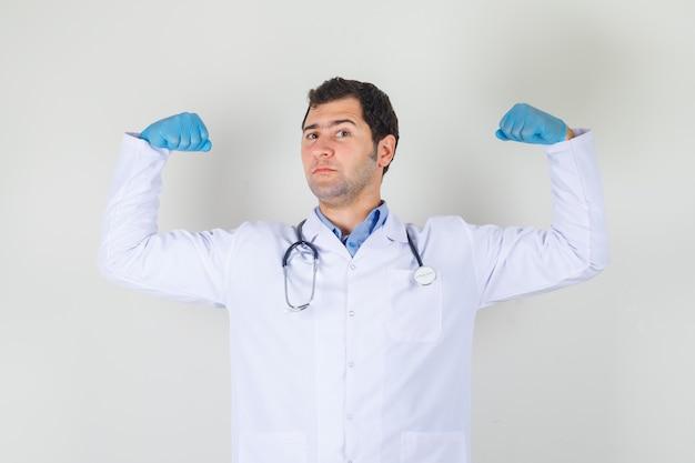 Médico homem com jaleco branco, luvas mostrando os músculos, levantando as mãos e parecendo orgulhoso