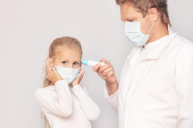Médico homem com máscara médica mede a temperatura de uma menina usando um termômetro eletrônico em um fundo isolado