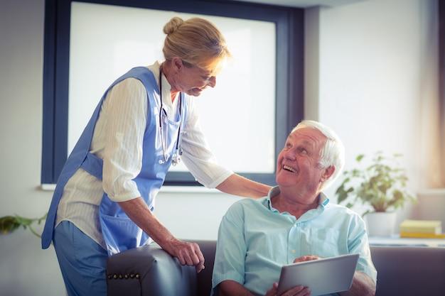 Médico homem e mulher sênior interagindo uns com os outros