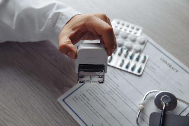 Médico homem em consultório médico público está carimbando contrato médico. conceito de saúde e medicina