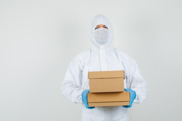 Médico homem em traje de proteção, luvas, máscara segurando caixas de papelão
