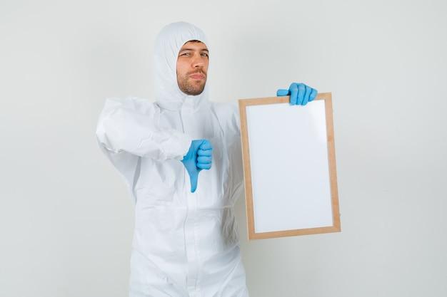 Médico homem em traje de proteção, luvas segurando uma moldura em branco com o polegar para baixo