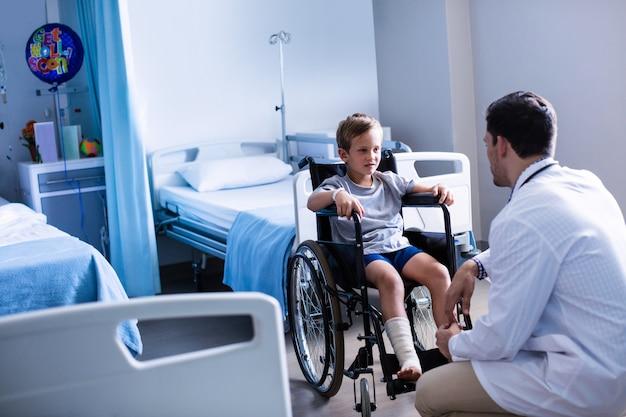 Médico homem interagindo com paciente criança na enfermaria