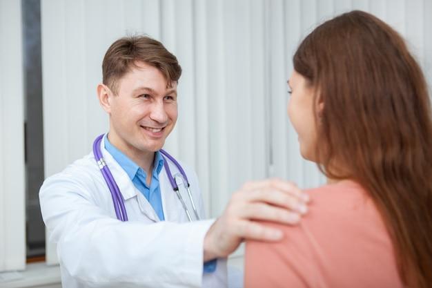 Médico homem maduro animando mulher jovem, ajudando-a a ficar mais saudável