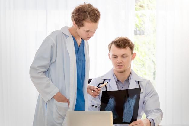 Médico homem segurando raio-x e conversa sobre o paciente com a mulher jovem médico.