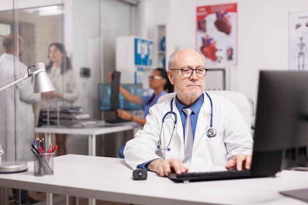 Médico idoso com estetoscópio trabalhando no computador no escritório da clínica enquanto o jovem médico está discutindo o relacionamento da doença com o paciente no corredor do hospital e a enfermeira está segurando o raio-x do homem doente.