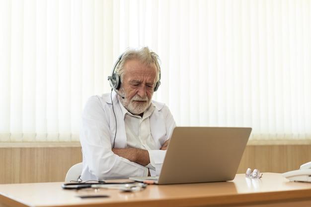 Médico idoso sênior usa fone de ouvido consulta remota por bate-papo médico on-line, conceito de telessaúde