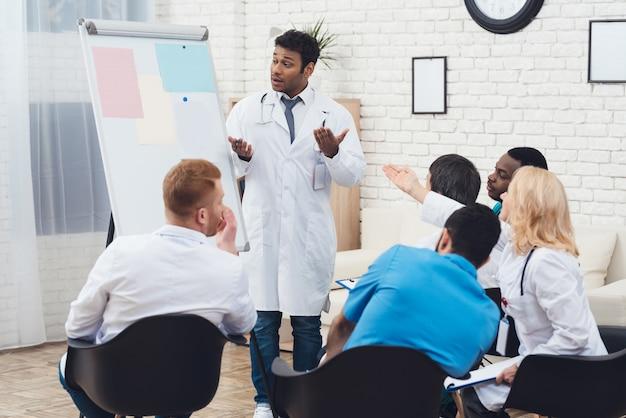 Médico indiano aconselha colegas durante uma reunião médica.