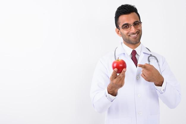 Médico indiano jovem bonito contra o fundo branco