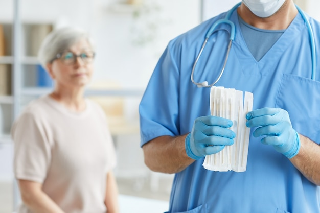 Médico irreconhecível com uniforme azul e luvas tirando uma vara de teste para uma paciente idosa sentada atrás dele