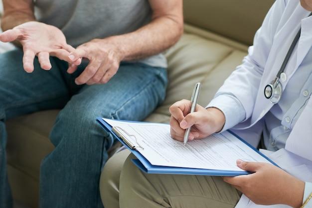 Médico irreconhecível, conversando com o paciente em casa e fazendo anotações